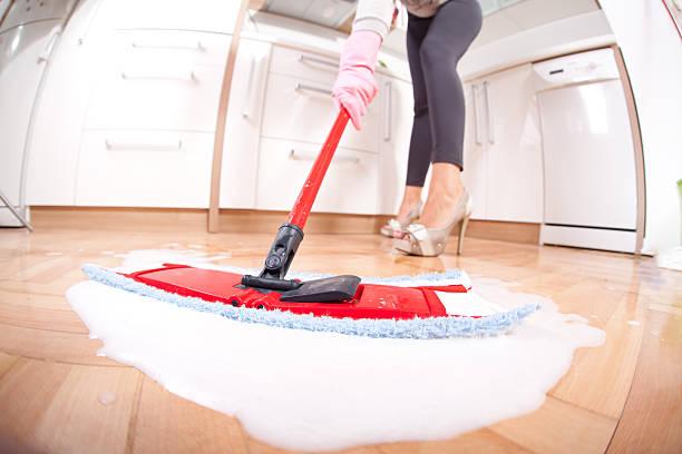 Girl in high heels, washing the wooden kitchen floor